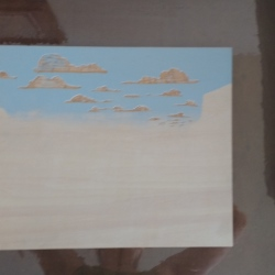 This blurry image is of the first layer on the block, which I used a stencil for. The stencil protected the lower part of the block from receiving ink, so the blue ink was only applied to the upper section. I did this because I wanted a soft gradient for the sky's edge; if this was carved, it would have a crisp edge.
